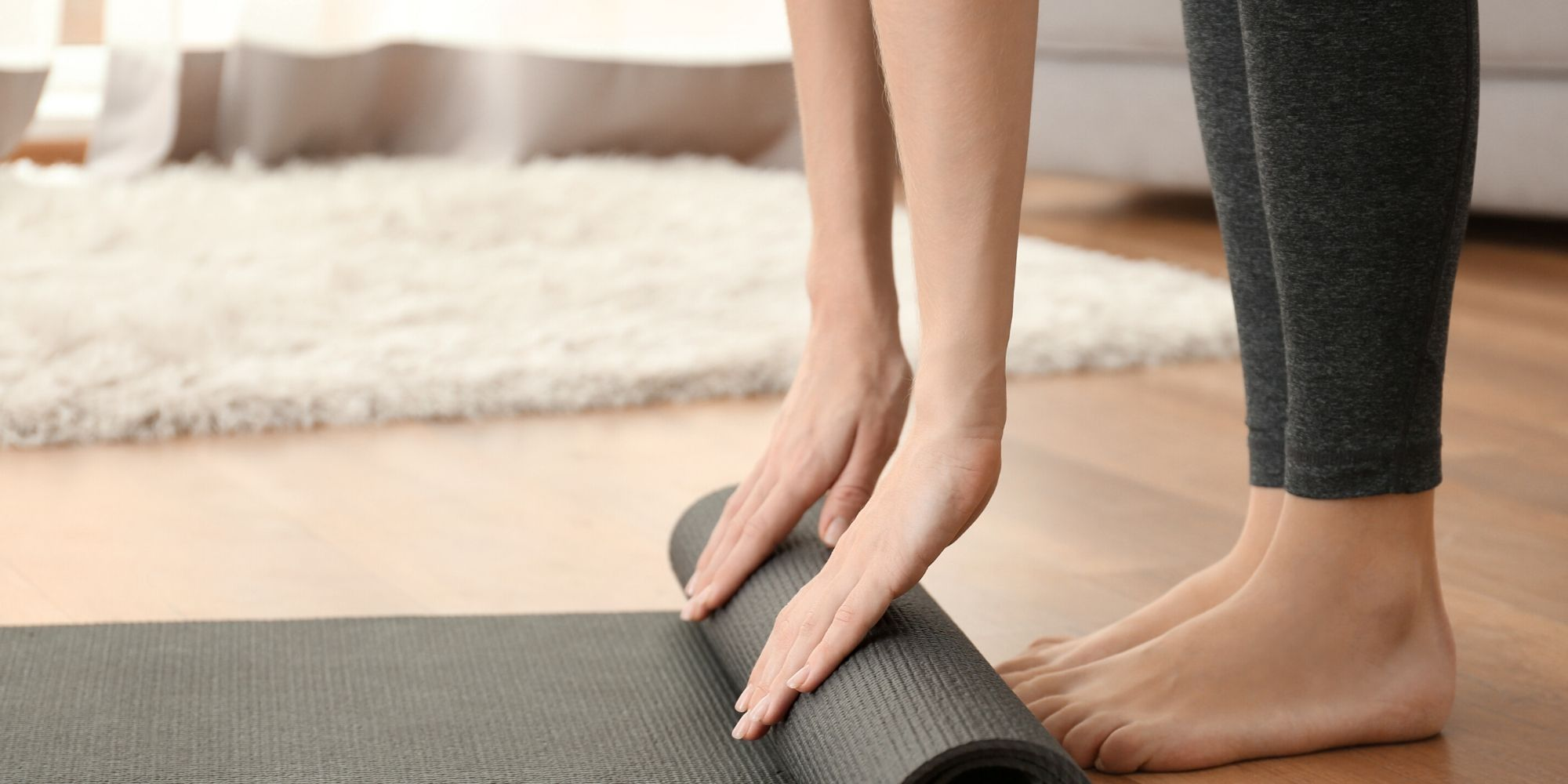 Woman unrolling yoga mat at home